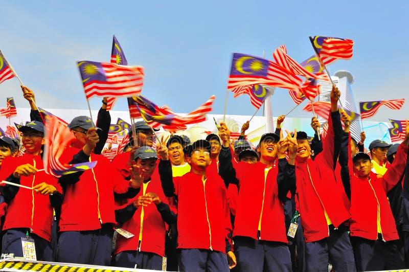 Étudiants ondulant des indicateurs de la Malaisie pendant le jour national photographie stock