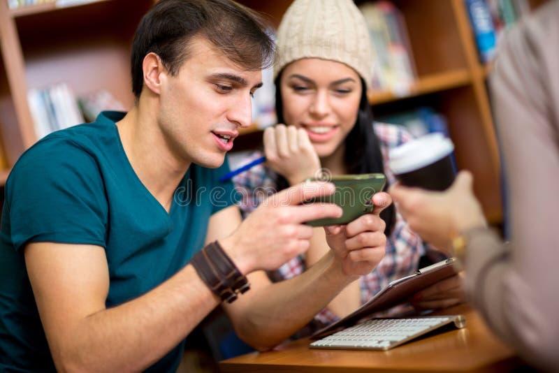 Étudiants regardant dans le message drôle au téléphone portable photographie stock libre de droits