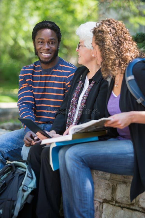 Étudiants s'asseyant avec le professeur photo stock