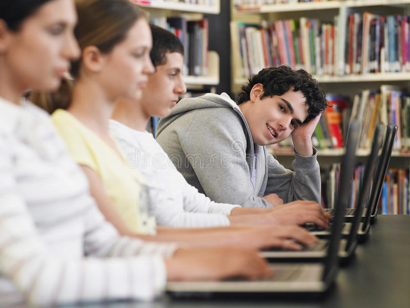 Étudiants s'asseyant dans la rangée utilisant des ordinateurs portables dans la bibliothèque photos libres de droits
