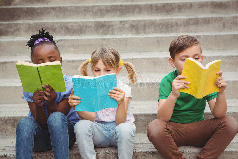 Étudiants s'asseyant sur des étapes et des livres de lecture photo stock