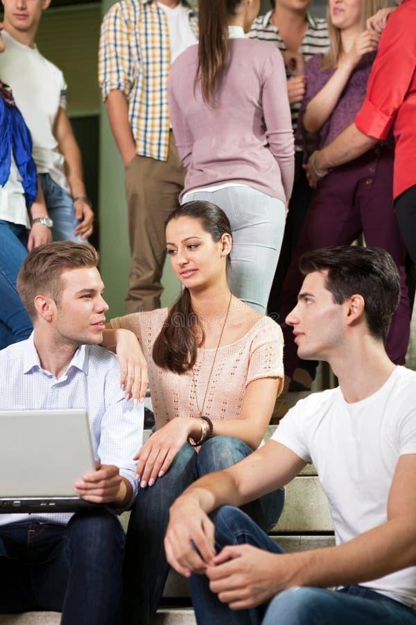Étudiants s'asseyant sur des escaliers de lycée dans la coupure images stock