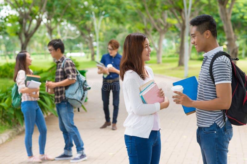 étudiants s'asseyants extérieurs d'université de campus de banc photos stock