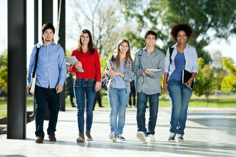 Étudiants sûrs marchant dans une rangée sur le campus images libres de droits