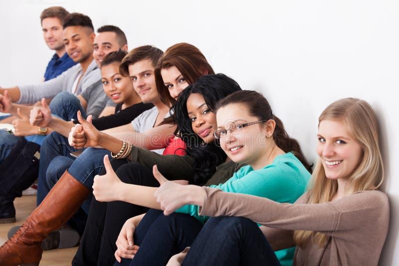 Étudiants sûrs s'asseyant dans une rangée photo libre de droits