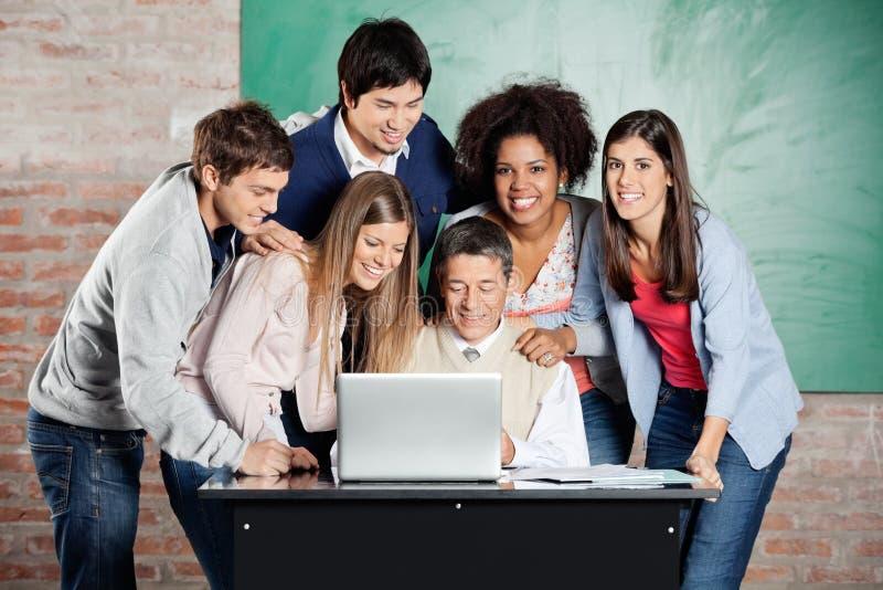 Étudiants se tenant avec des camarades de classe tandis que professeur images stock