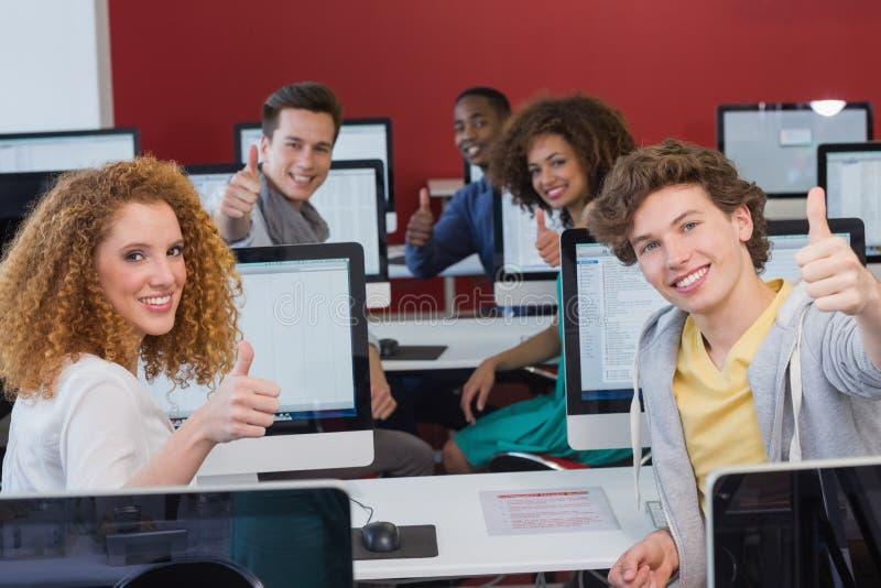 Étudiants souriant à l'appareil-photo dans la classe d'ordinateur images stock