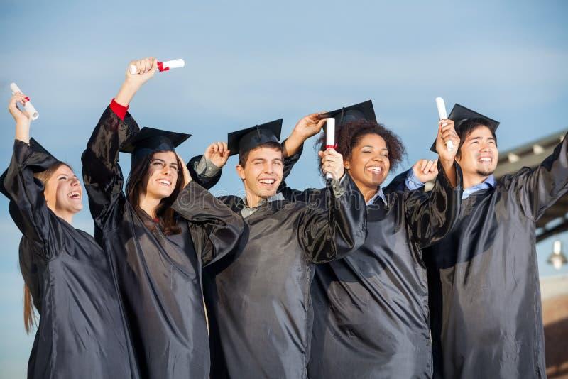 Étudiants tenant des certificats contre le ciel photographie stock