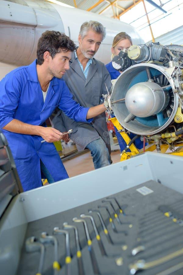 Étudiants travaillant à la turbine d'avions photos stock
