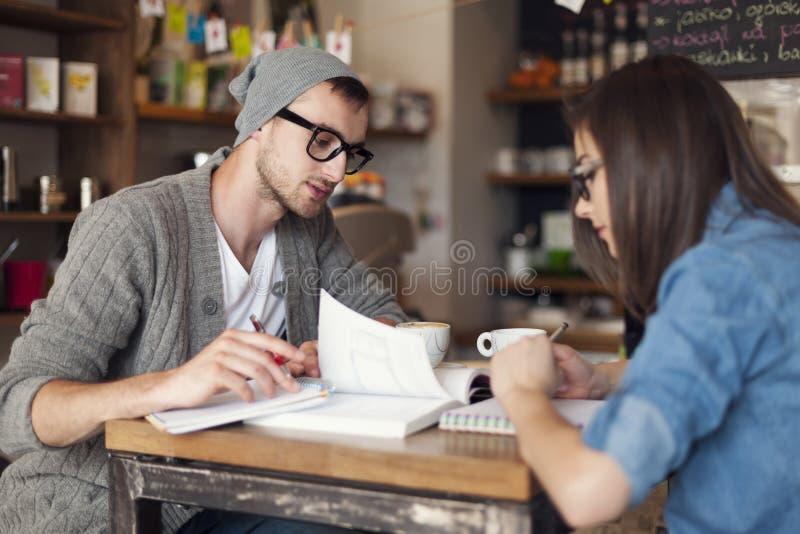 Étudiants travaillant au café images stock