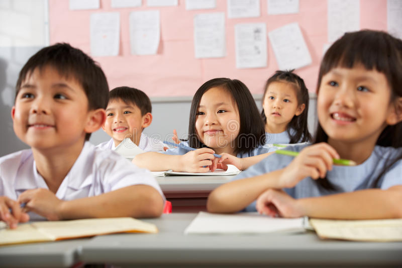 Étudiants travaillant aux bureaux à l'école chinoise photos libres de droits