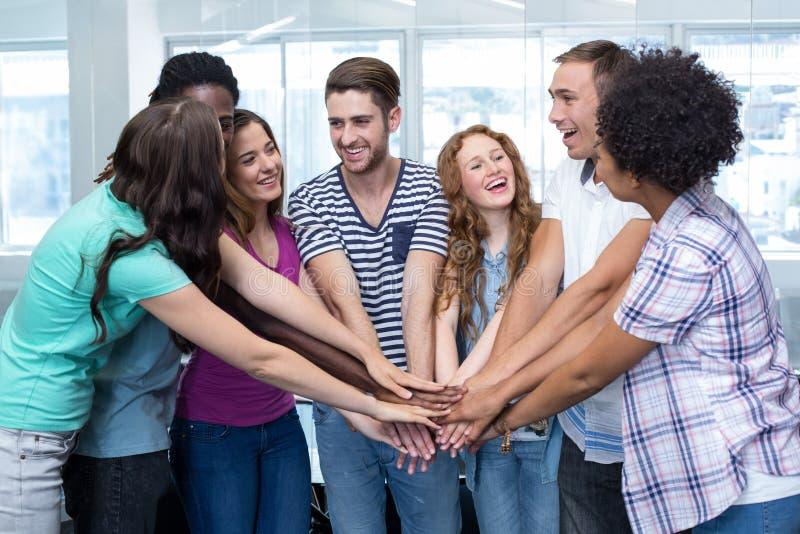 Étudiants universitaires heureux plaçant des mains ensemble image libre de droits