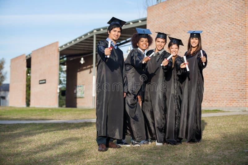 Étudiants universitaires montrant des diplômes se tenant dessus image libre de droits