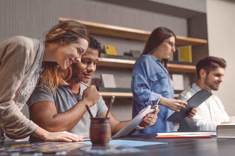 Étudiants universitaires s'asseyant ensemble et étudiant image libre de droits