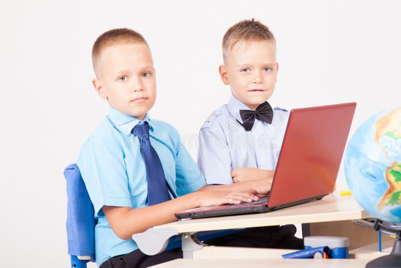 Étudiez sur les garçons de l'ordinateur deux à l'école image libre de droits