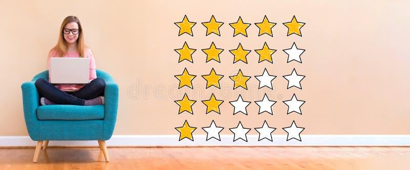 Évaluation avec les étoiles jaunes avec la femme à l'aide d'un ordinateur portable photographie stock
