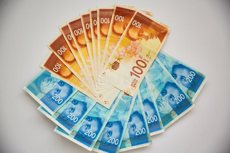 Éventé - argent israélien - fond d'une pile de billets de banque israéliens de factures d'argent de, du shekel 100 et 200 sur le  image stock
