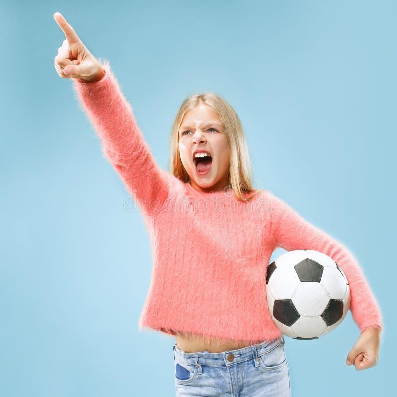 Éventez le joueur de l'adolescence de sport jugeant le ballon de football d'isolement sur le fond bleu photographie stock