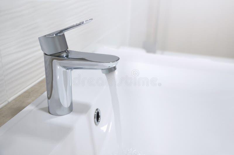 Évier avec un robinet de chrome duquel un courant des écoulements d'eau image photos stock