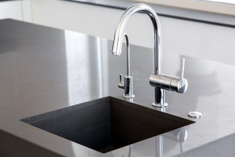 Évier de cuisine de pierre gris-foncé avec le robinet de chrome photo libre de droits
