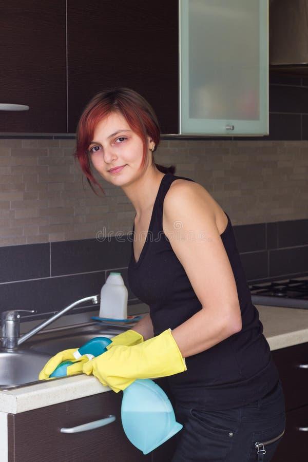 Évier de nettoyage de jeune fille dans la cuisine photo stock