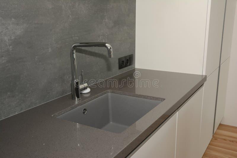 Évier et eau du robinet de cuisine noirs dans la cuisine Robinet en métal de cuisine et évier de cuisine modernes image libre de droits