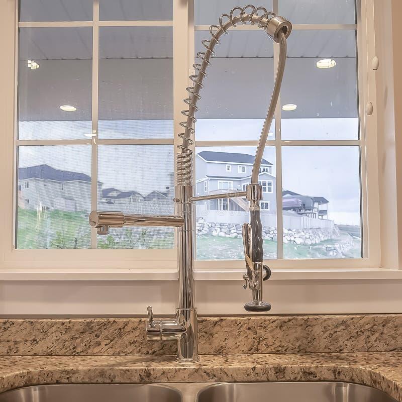Évier et robinet de bassin d'acier inoxydable de place doubles à l'intérieur de la cuisine d'une maison photographie stock libre de droits
