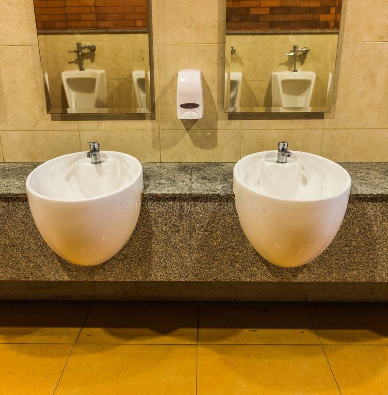 Éviers blancs et savon liquide dans la toilette publique images stock