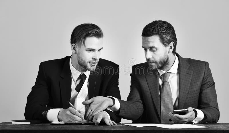 Éxito, ayuda, concepto de la sociedad El hombre de negocios consulta con el experto financiero que tiene cara seria fotos de archivo