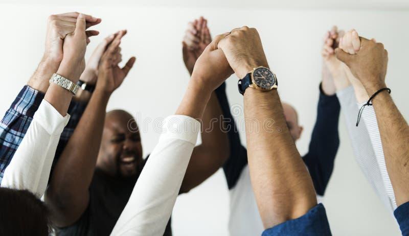 Éxito de las manos de la gente diversa junto y concepto de la celebración que se unen a foto de archivo libre de regalías