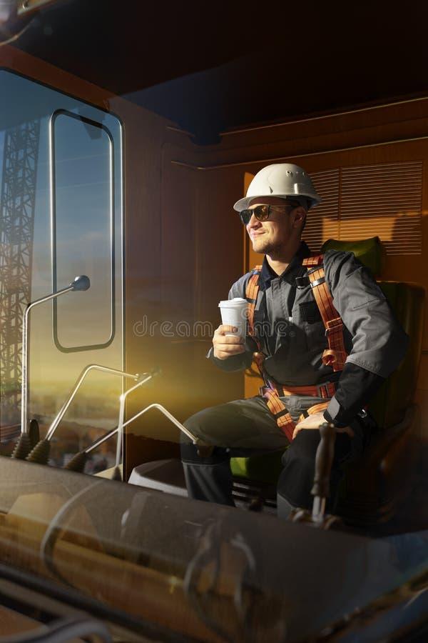 Éxito feliz de la sensación del ingeniero después del buen trabajo Él sienta un top en cabina de la grúa bebe el café caliente y  foto de archivo libre de regalías