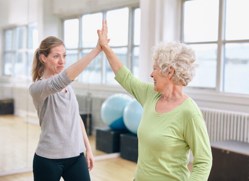 Éxito mayor de la salud del júbilo de la mujer con su instructor en la rehabilitación fotografía de archivo libre de regalías