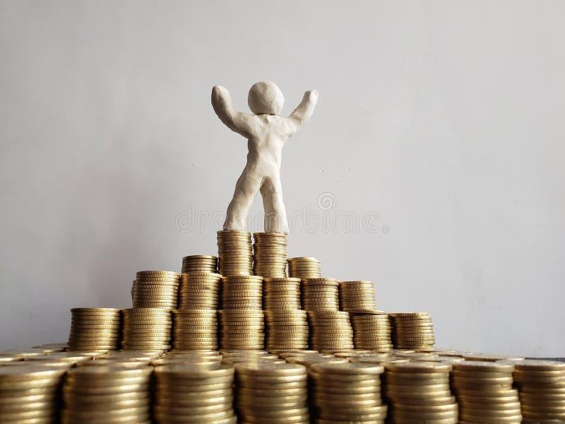 éxito y desarrollo económico, una figura humana del plasticine blanco y monedas apiladas de Pesos mexicanos imagenes de archivo