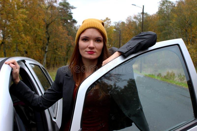 Être prêt Portrait de la jeune dame de sourire tenant la porte proche de voiture et d'ouverture images libres de droits