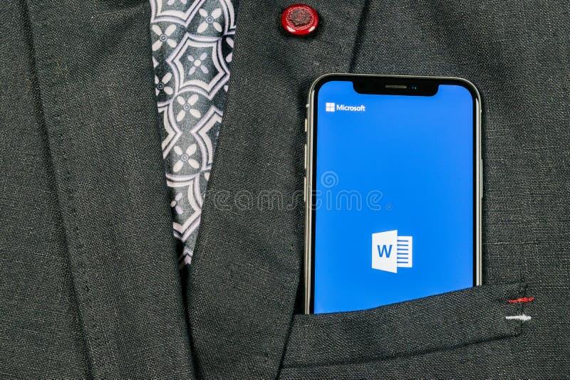 Ícone da aplicação de Microsoft Word no close-up da tela do iPhone X de Apple no bolso do revestimento Ícone da palavra do Micros fotografia de stock royalty free