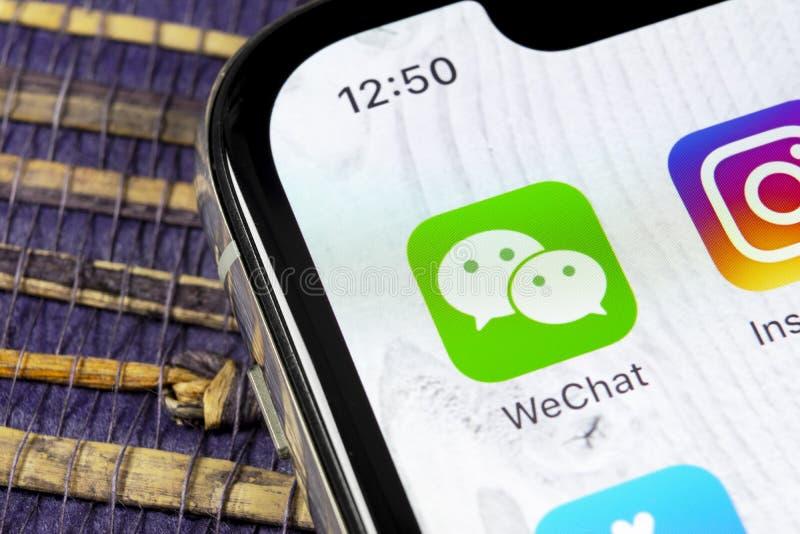 Ícone da aplicação do mensageiro de Wechat no close-up da tela do smartphone do iPhone X de Apple Ícone do app do mensageiro de W imagens de stock royalty free
