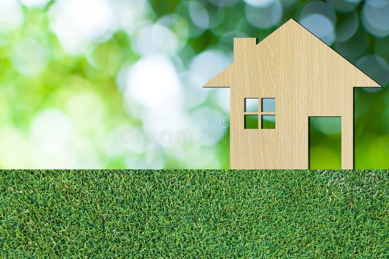 Ícone da casa de madeira no fundo da natureza da textura da grama como o símbolo da hipoteca imagem de stock royalty free