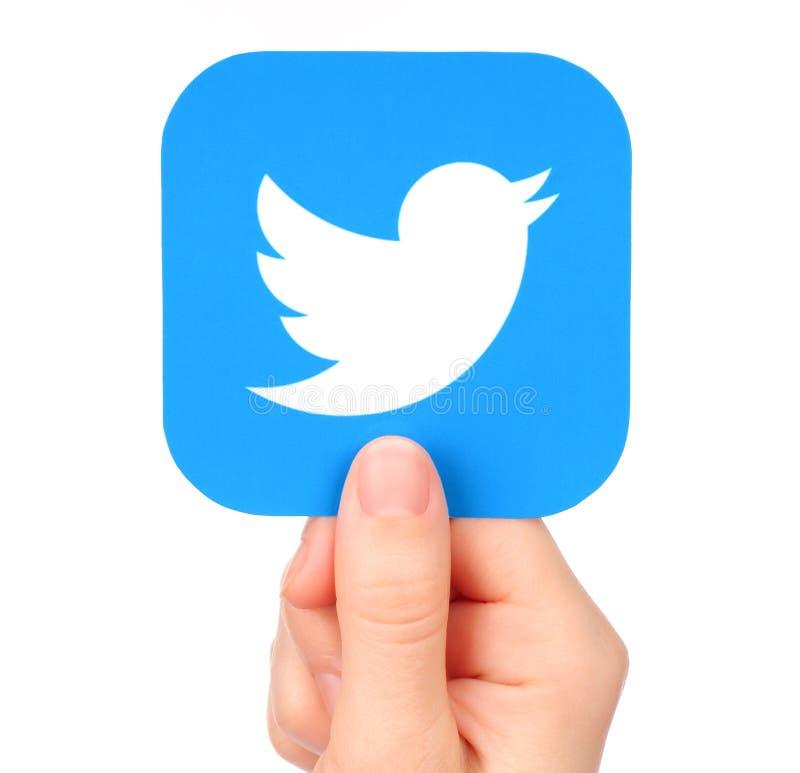 Ícone de Twitter das posses da mão impresso no papel imagem de stock