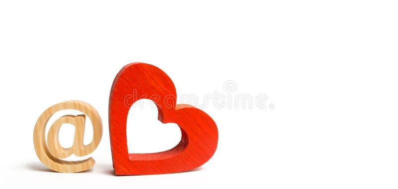 Ícone do e-mail e coração de madeira vermelho Internet que data o conceito Amor em linha Busca para a segunda metade Familiaridad fotos de stock