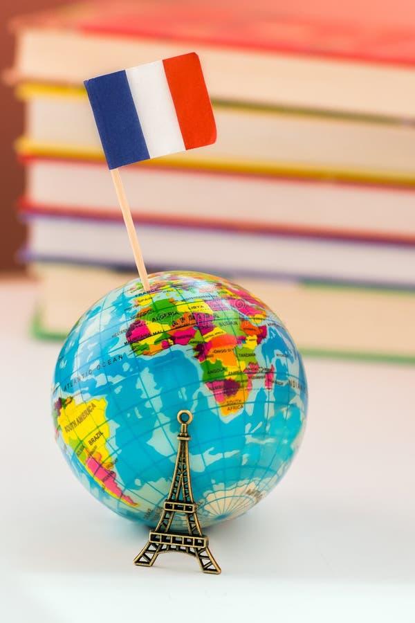 Ícone do globo a torre Eiffel no fundo dos livros e dos livros de texto Aprenda o francês Cursos de línguas francesas, prática em fotos de stock
