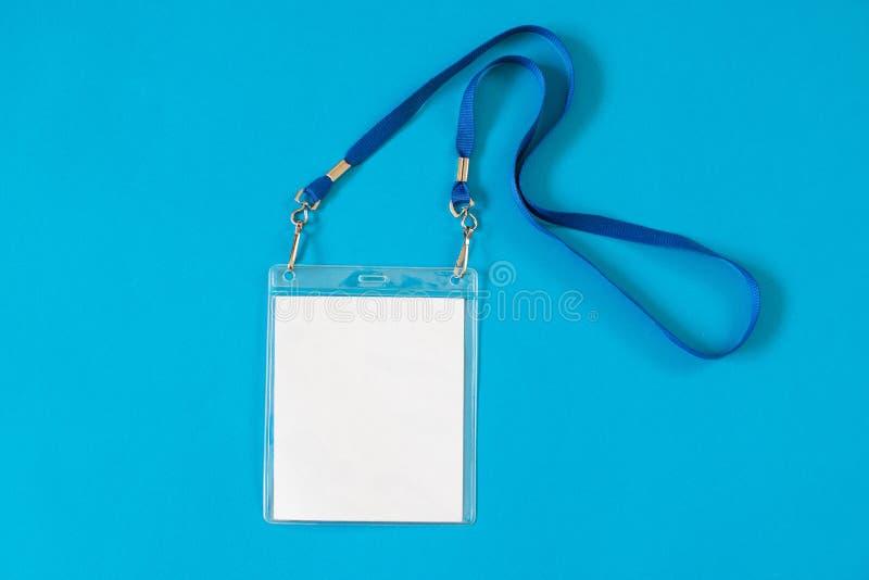 Ícone vazio do crachá do cartão da identificação com correia azul, no fundo azul fotografia de stock royalty free