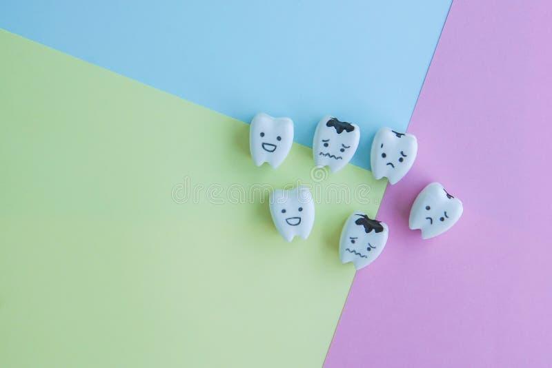 Ícones dos dentes saudáveis e deteriorados no fundo pastel para a educação da criança foto de stock