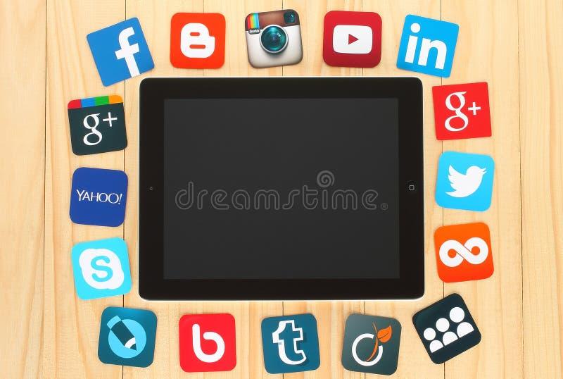 Ícones sociais famosos dos meios colocados em torno do iPad ilustração stock