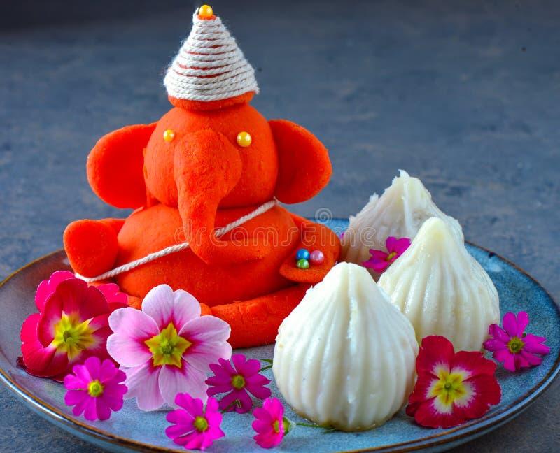 Ídolo amigável de Eco do senhor Ganesha com doce e flores do modak fotos de stock royalty free