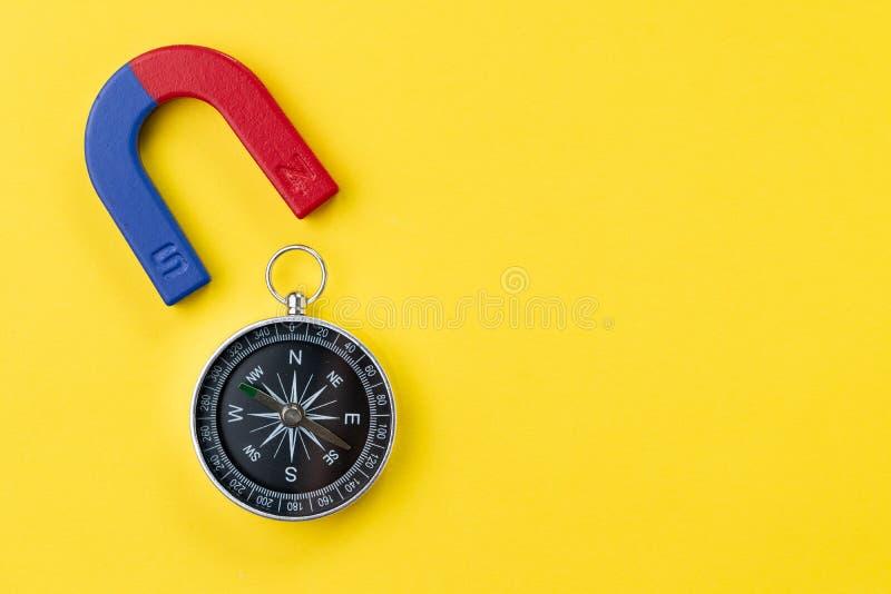 Ímã em ferradura com azul e o vermelho com compasso no fundo amarelo vívido com espaço da cópia usando-se para a força especial o imagens de stock