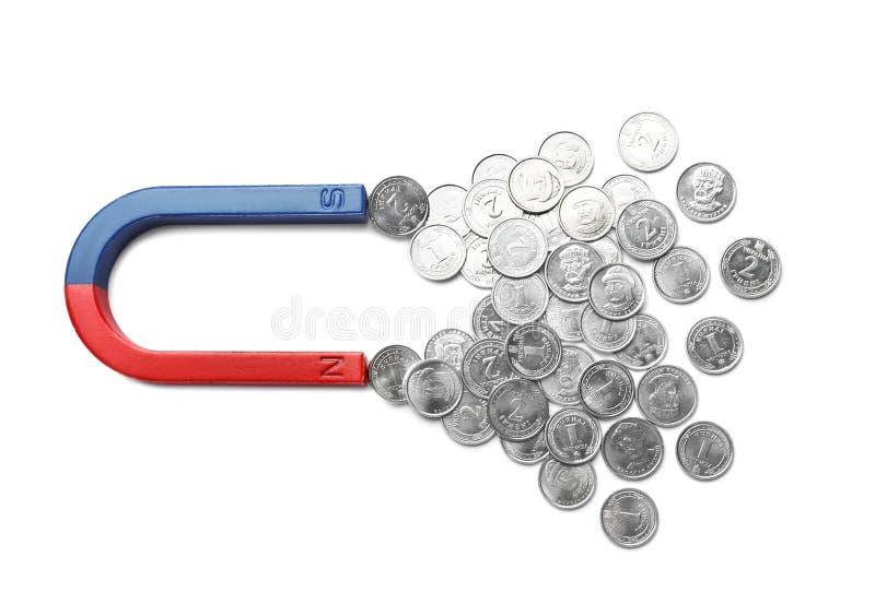 Ímã que atrai moedas no fundo branco Conceito do neg?cio imagem de stock royalty free