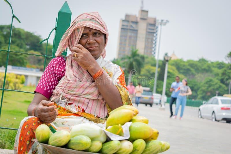 Índia de Bangalore, Karnataka 4 de junho de 2019: Mulher do vendedor ambulante que vende a manga e o pepino no dia ensolarado que foto de stock
