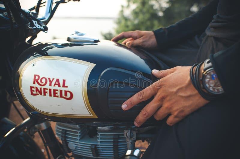 Índia, Goa - 6 de abril de 2017: Equipe a mão do ` s com um relógio no depósito de gasolina da motocicleta real de Enfield foto de stock