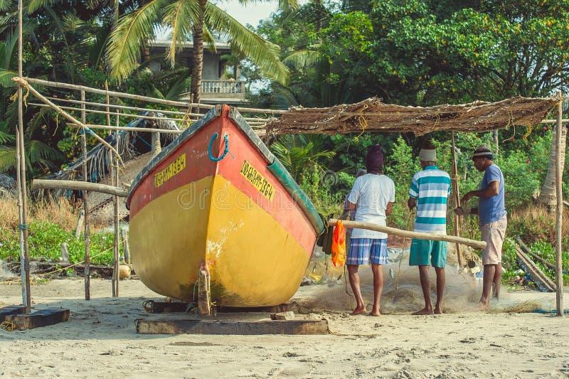 Índia, Goa - 19 de novembro de 2016: Redes do weave dos pescadores perto de um barco amarelo imagem de stock