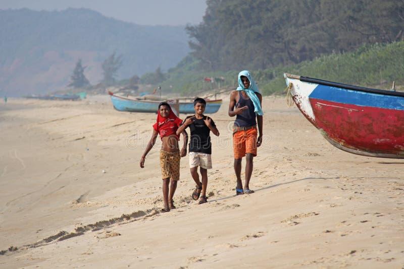 Índia, GOA, o 22 de janeiro de 2018 As crianças indianas estão andando ao longo do litoral Barcos na praia ou na praia imagem de stock